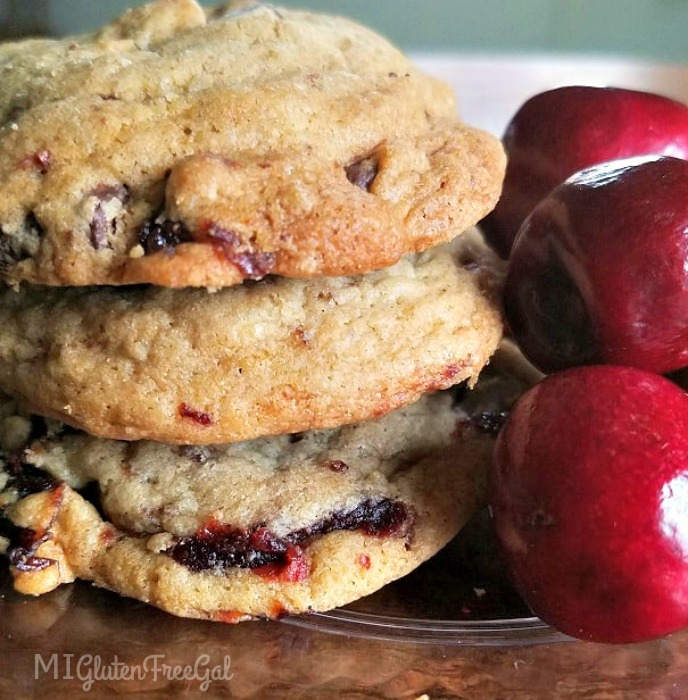 Gluten-Free Cherry Chocolate Chunk Cookies stacked next to fresh cherries